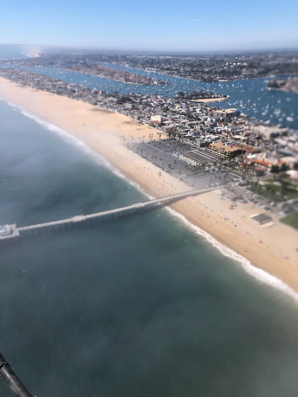 from a helicopter overlooking the Balboa Pier and parking lot between 2 and 230 saturday